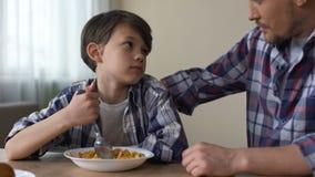 Copos de maíz de mezcla del pequeño muchacho triste con la cuchara, mirando al padre, apetito pobre almacen de metraje de vídeo