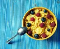 Copos de maíz y diversas bayas - arándanos y frambuesas frescas, fondo de madera azul Buen desayuno Imagen de archivo libre de regalías