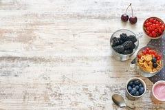 Copos de maíz, yogur y bayas en una tabla de madera Fotos de archivo libres de regalías
