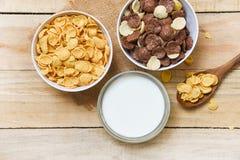 Copos de ma?z del desayuno y diversos cereales en taza del cuenco y de la leche en el fondo de madera para la comida sana del cer foto de archivo libre de regalías