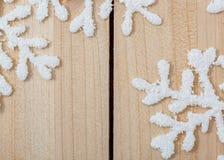 Copos de nieve artificiales blancos en una tabla de madera ligera Año Nuevo y fondo de la decoración de la Navidad y espacio de l foto de archivo