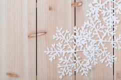 Copos de nieve artificiales blancos en una tabla de madera ligera Fondo de la decoraci?n de la Navidad y espacio de la copia para imágenes de archivo libres de regalías