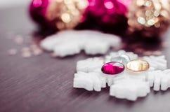 Copos de nieve blancos en el fondo de las chucherías de Navidad de la magenta y del oro Fotografía de archivo