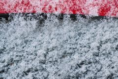 Copos de nieve blancos, nieve sobre el vidrio negro y metal rojo, abstracto Imagen de archivo libre de regalías