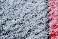 Copos de nieve blancos, nieve sobre el vidrio negro y metal rojo, abstracto Foto de archivo libre de regalías