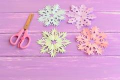 Copos de nieve cortados del papel coloreado Copos de nieve de papel rosados, verdes, azules y púrpuras, tijeras en la tabla de ma Fotos de archivo
