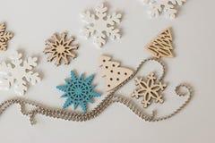 Copos de nieve de madera decorativos y un árbol de navidad con una secuencia Imagen de archivo