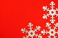 Copos de nieve de madera en el fondo festivo colorido superficial natural de lino rojo con el espacio para el texto Imagen de archivo