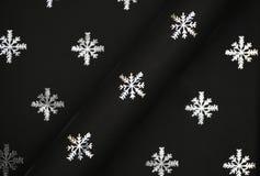 Copos de nieve de plata en el papel negro Fotografía de archivo