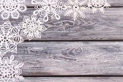 Copos de nieve decorativos blancos en viejo fondo de madera del vintage Fotografía de archivo libre de regalías