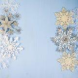 Copos de nieve decorativos de plata en un fondo de madera azul cristo Foto de archivo libre de regalías