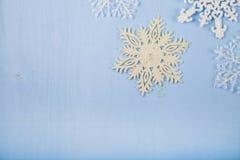 Copos de nieve decorativos de plata en un fondo de madera azul cristo Imagen de archivo libre de regalías