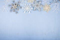 Copos de nieve decorativos de plata en un fondo de madera azul cristo Fotos de archivo libres de regalías