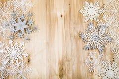 Copos de nieve decorativos de plata en un fondo de madera azul cristo Imagenes de archivo