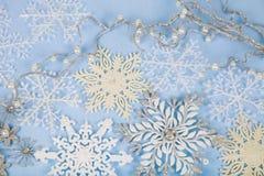 Copos de nieve decorativos de plata en un fondo de madera azul cristo Fotografía de archivo