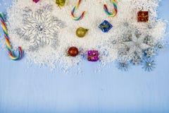 Copos de nieve decorativos de plata en un fondo de madera azul cristo Imágenes de archivo libres de regalías