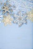 Copos de nieve decorativos de plata en un fondo de madera azul cristo Imagen de archivo