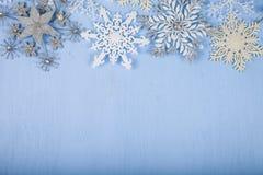 Copos de nieve decorativos de plata en un fondo de madera azul cristo Fotos de archivo