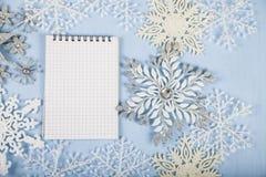 Copos de nieve decorativos de plata y un cuaderno en un CCB de madera azul Imagen de archivo libre de regalías