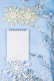 Copos de nieve decorativos de plata y un cuaderno en un CCB de madera azul Foto de archivo