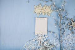 Copos de nieve decorativos de plata y un cuaderno en un CCB de madera azul Imágenes de archivo libres de regalías