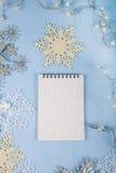 Copos de nieve decorativos de plata y un cuaderno en un CCB de madera azul Fotos de archivo libres de regalías