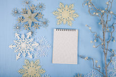 Copos de nieve decorativos de plata y un cuaderno en un CCB de madera azul Imagenes de archivo
