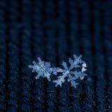Copos de nieve en tela texturizada Fotos de archivo libres de regalías
