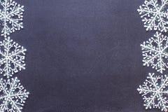 Copos de nieve en una pizarra negra Foto de archivo libre de regalías