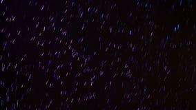 Copos de nieve que caen teniendo en cuenta proyectores azules y púrpuras La nieve cae contra un cielo oscuro Abstraiga el fondo c almacen de metraje de vídeo