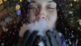 Copos de nieve que soplan de la mujer joven de sus manos que hacen una pausa el árbol de navidad Concepto de la celebración de la almacen de video