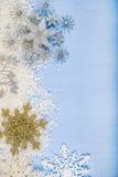 Copos de nieve y nieve decorativos de plata en un backgroun de madera azul Foto de archivo