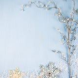 Copos de nieve y rama decorativos de plata en un backgro de madera azul Foto de archivo