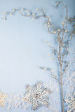 Copos de nieve y rama decorativos de plata en un backgro de madera azul Fotografía de archivo libre de regalías