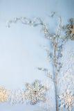 Copos de nieve y rama decorativos de plata en un backgro de madera azul Imagen de archivo libre de regalías