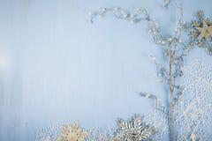 Copos de nieve y rama decorativos de plata en un backgro de madera azul Foto de archivo libre de regalías