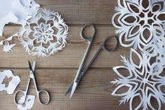 Copos de nieve y tijeras del papel hecho a mano Fotografía de archivo