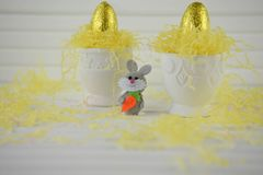 Copos de ovo com os ovos da páscoa de chocolate dourados da cor no branco Fotografia de Stock