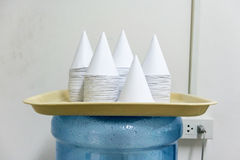Copos de papel descartáveis de forma de cone na luz - bandeja amarela Imagem de Stock