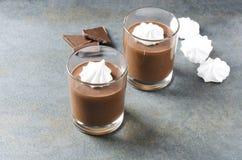 Copos de vidro do moussein dois do chocolate, partes de merengue do nad do chocolate na tabela cinzenta rústica fotos de stock royalty free