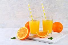 Copos de vidro e um jarro do suco de laranja fresco com fatias de tubos alaranjados e amarelos em uma luz - tabela cinzenta imagem de stock royalty free