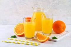 Copos de vidro e um jarro do suco de laranja fresco com fatias de tubos alaranjados e amarelos em uma luz - tabela cinzenta fotografia de stock