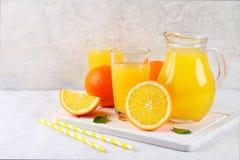 Copos de vidro e um jarro do suco de laranja fresco com fatias de tubos alaranjados e amarelos em uma luz - tabela cinzenta foto de stock