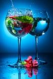 Copos de vinho com água e as flores Imagens de Stock Royalty Free