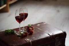 Copos de vinho com o vinho tinto decorado com morango e hortelã Foto de Stock