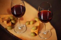 Copos de vinho com vinho tinto na madeira com queijo e azeitonas verdes - para a noite home acolhedor Fotografia de Stock