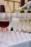 Copos de vinho derramados com vinho tinto e champanhe na tabela Imagens de Stock Royalty Free
