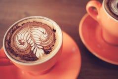 Copos do café do cappuccino na madeira do marrom escuro Foto de Stock