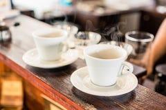 Copos do café do gotejamento na barra da cafetaria Fotos de Stock