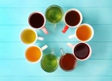 Copos do chá diferente na tabela de madeira, Fotos de Stock Royalty Free